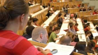 Viele junge Menschen sitzen in einem großen Raum.