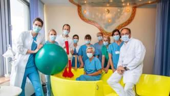 Zehn Personen in medizinischer Arbeitskleidung